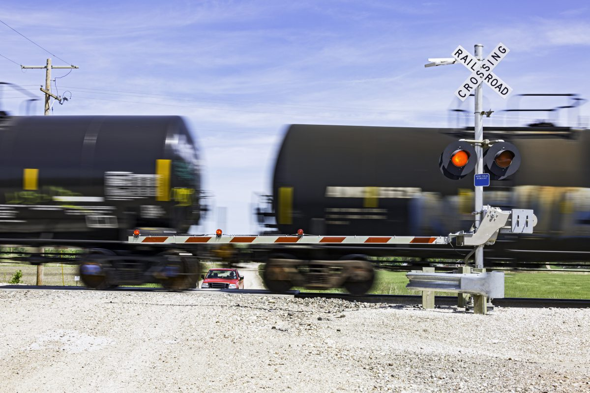 Hazardous rail freight passes crossing on rural road.